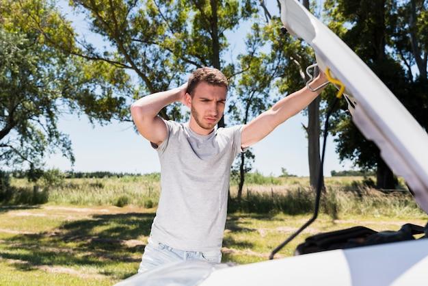 Junge, der aufgeschlüsseltes auto betrachtet Kostenlose Fotos