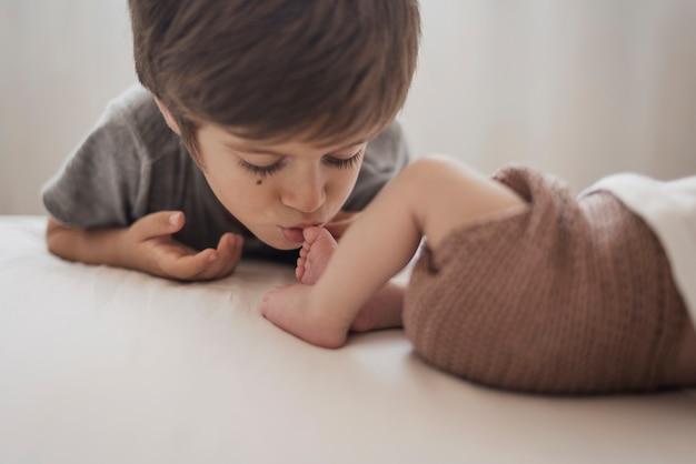 Junge, der bein des kleinen bruders küsst Kostenlose Fotos