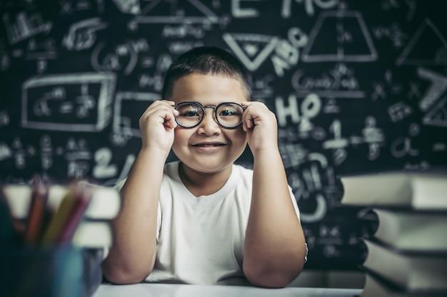 Junge, der brillenbein im klassenzimmer studiert und hält. Kostenlose Fotos