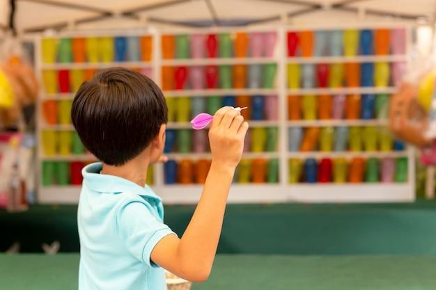 Junge, der das pfeilspiel mit mehrfarbenballonen an der messe spielt. Premium Fotos