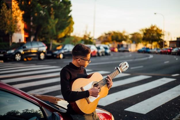 Junge, der die gitarre durch die stadt von madrid, spanien spielt. Premium Fotos