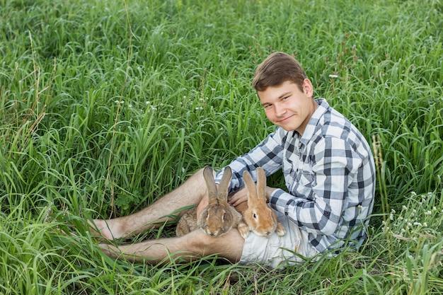Junge, der die kamera hält kaninchen betrachtet Kostenlose Fotos