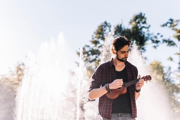 Junge, der die ukulele spielt Kostenlose Fotos