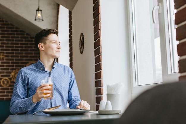 Junge, der ein bier in einem restaurant isst Kostenlose Fotos