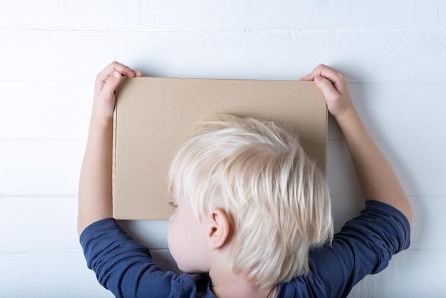 Junge, der ein paket umarmt. nettes kind, das einen kasten anhält. , ansicht von oben Premium Fotos