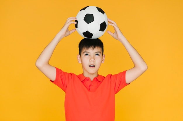 Junge, der eine fußballkugel auf seinem kopf anhält Kostenlose Fotos
