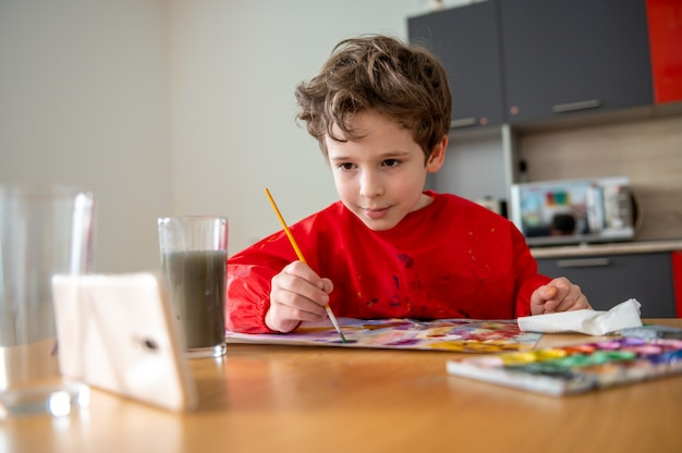 Junge, der fleißig mit online-fernunterricht zeichnet Premium Fotos