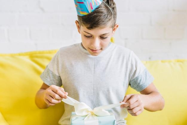 Junge, der geschenk während seines geburtstages auspackt Kostenlose Fotos