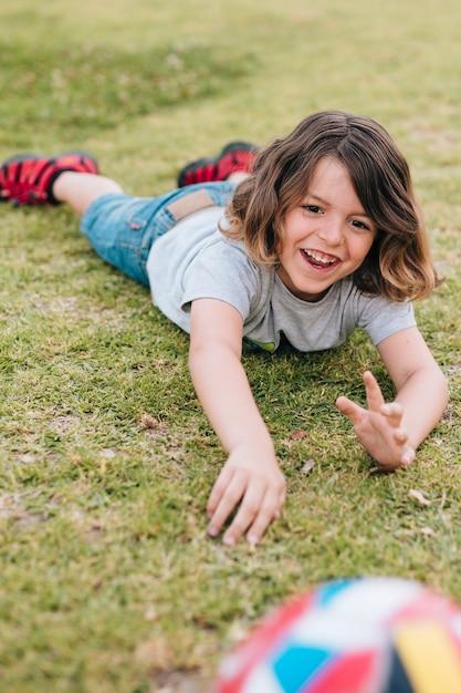 Junge, der im gras liegt und mit ball spielt Kostenlose Fotos