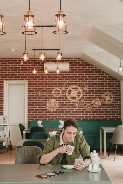 Junge, der kaffee in einem restaurant trinkt Kostenlose Fotos