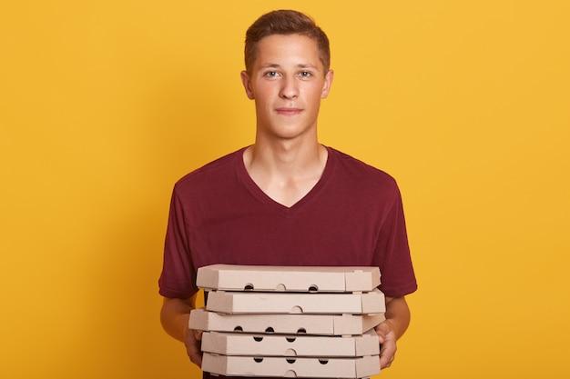 Junge, der kastanienbraunes lässiges t-shirt trägt, das pizzaschachteln liefert, lokalisiert auf gelb posiert, kamera betrachtet, sieht ernst aus, junge frau, die als lieferbote arbeitet und seine arbeit tut. personenkonzept Kostenlose Fotos