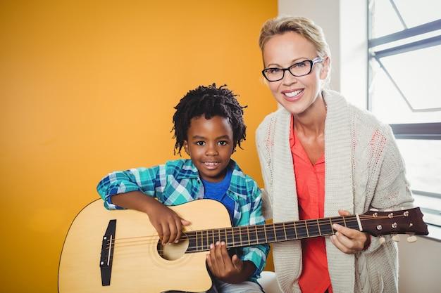 Junge, der lernt, wie man gitarre spielt Premium Fotos