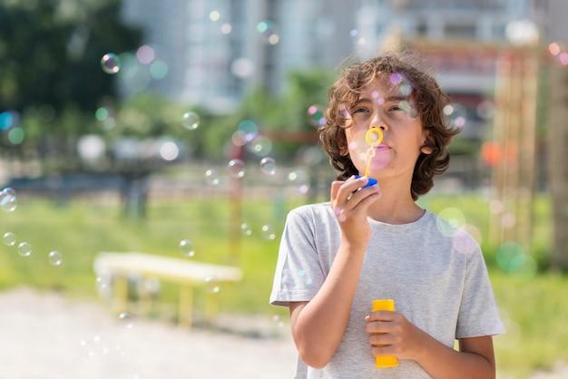 Junge, der mit blasengebläse im freien spielt Kostenlose Fotos