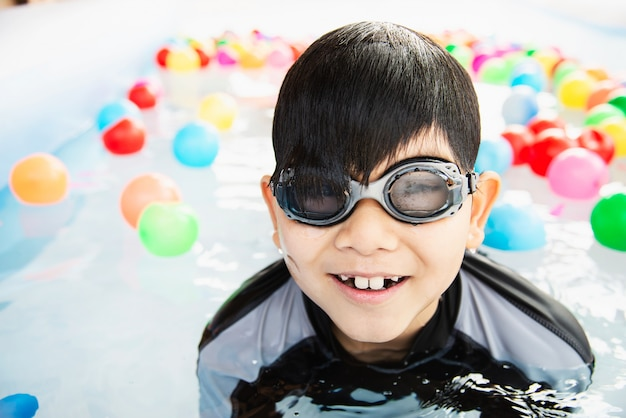 Junge, der mit buntem ball im kleinen swimmingpoolspielzeug spielt Kostenlose Fotos