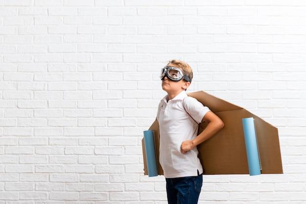 Junge, der mit den pappflugzeugflügeln aufwirft mit den armen an der hüfte spielt Premium Fotos