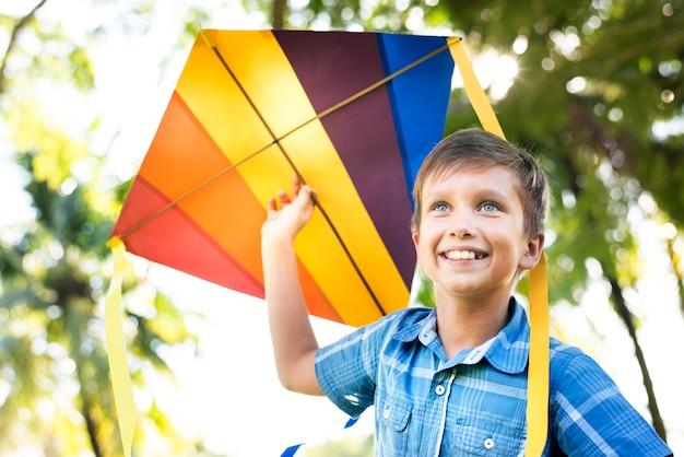 Junge, der mit einem bunten drachen spielt Premium Fotos