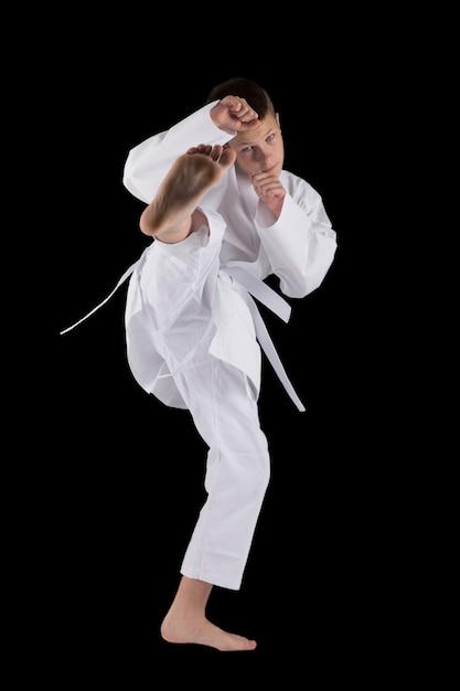 Junge, der mit karatetechniken im studio auf dem schwarzen lokalisiert aufwirft Premium Fotos