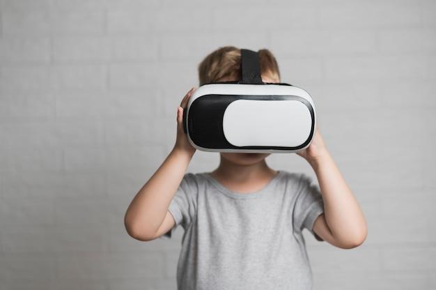 Junge, der mit kopfhörer der virtuellen realität spielt Kostenlose Fotos