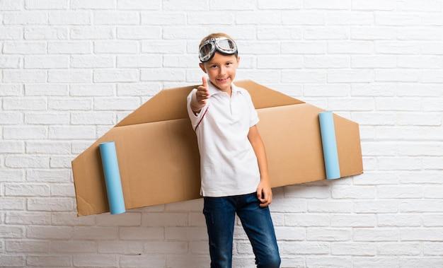Junge, der mit pappflugzeugflügel auf seinem hinteren händeschütteln nach gutem geschäft spielt Premium Fotos