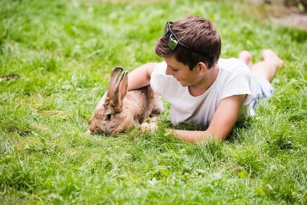 Junge, der mit seinem haustierkaninchen auf grünem gras liegt Kostenlose Fotos