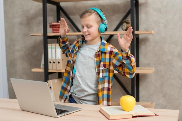 Junge, der musik auf laptop hört Kostenlose Fotos