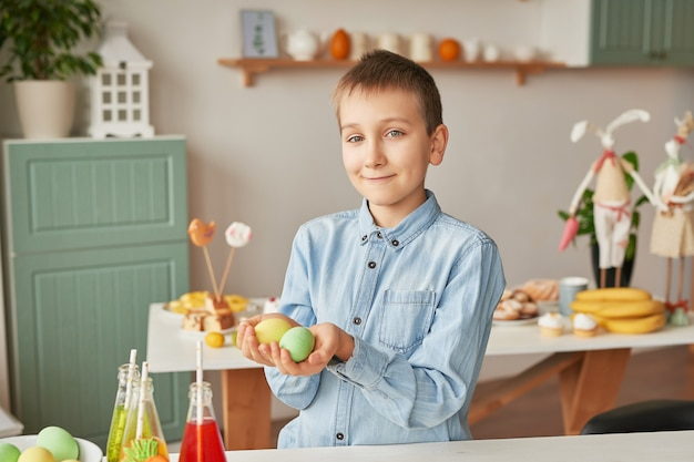 Junge, der ostereier an der küche hält Premium Fotos