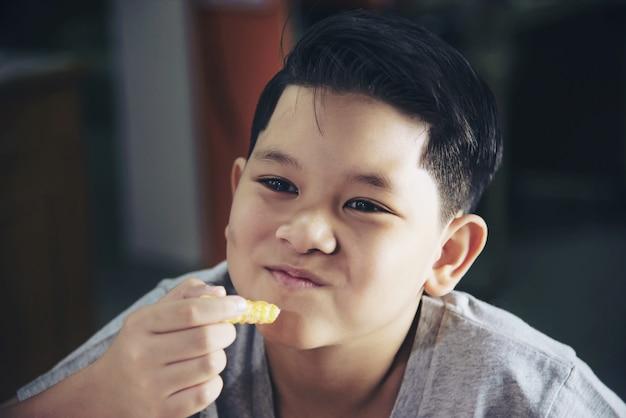 Junge, der pommes-friteskartoffel mit eingetauchter soße über weißem holztisch isst Kostenlose Fotos