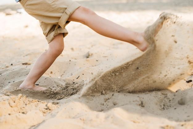 Junge, der sand am strand tritt Kostenlose Fotos