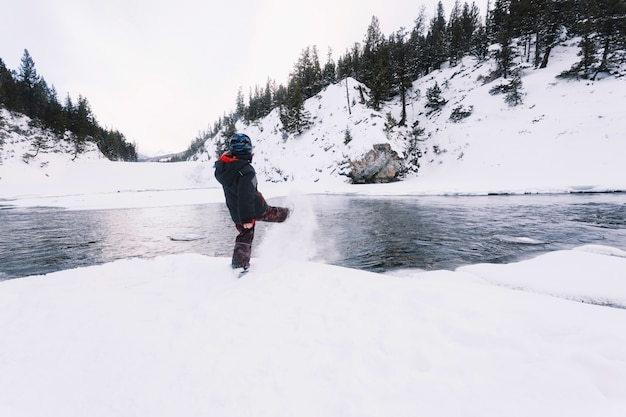 Junge, der schnee auf flussufer tritt Kostenlose Fotos