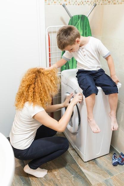 Junge, der seine mutter unter verwendung der waschmaschine betrachtet Kostenlose Fotos