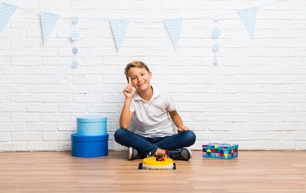 Junge, der seinen geburtstag mit einem kuchen zählt zeichen der nr. eine feiert Premium Fotos