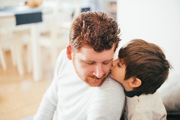 Junge, der vater auf wange küsst Kostenlose Fotos