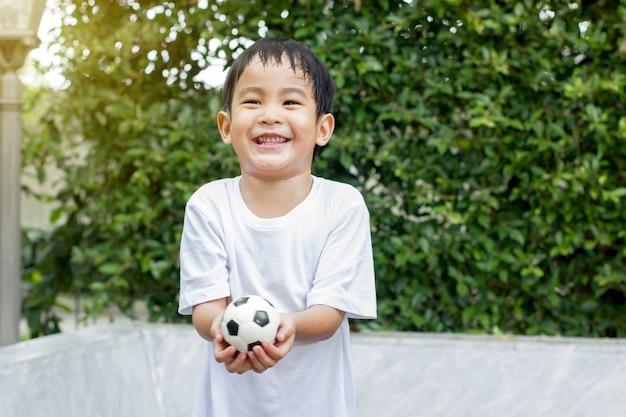 Junge, der vom spielen des kleinen fußballspielzeugs schwitzt und erschöpft ist. Premium Fotos