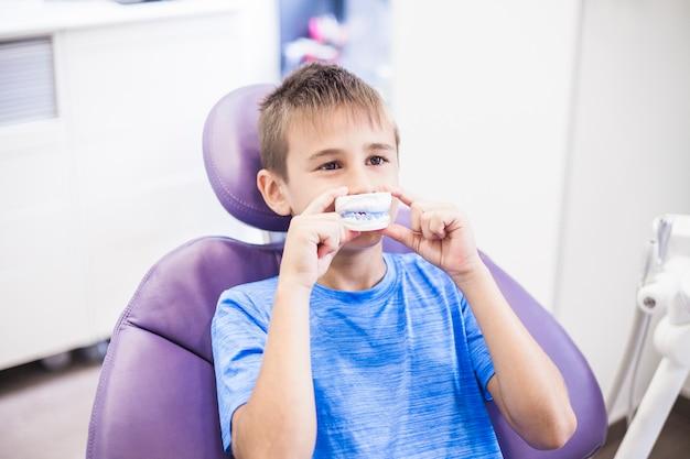 Junge, der zahnputzform vor seinem mund hält Kostenlose Fotos