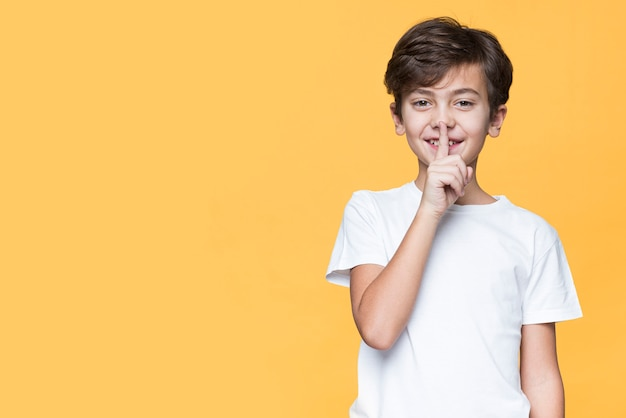 Junge, der zeichen für ruhe zeigt Kostenlose Fotos