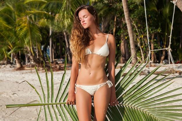Junge dünne frau in der weißen bikini-badebekleidung, die blatt der palme hält, die sich am tropischen strand sonnt. Kostenlose Fotos