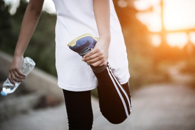 Junge eignungsfrauenhand, die wasserflasche hält, nachdem übung laufen gelassen worden ist Kostenlose Fotos