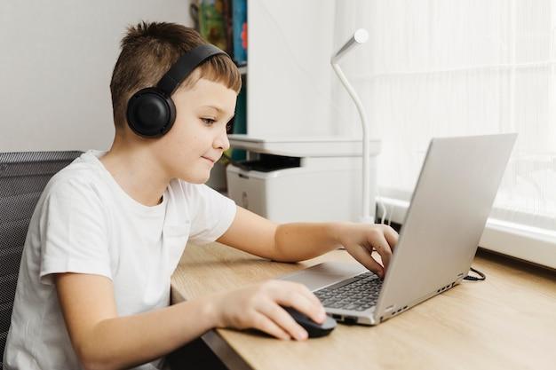 Junge ein zuhause mit laptop und kopfhörer Kostenlose Fotos