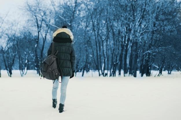Junge einsame frau mit rucksack gehend in den schneebedeckten wald des winters Premium Fotos