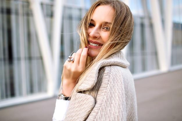 Junge elegante hübsche blonde frau posiert auf der straße, natürlicher sinnlicher blick, lächelt und schaut vor der kamera, trägt trendigen beigen mantel und luxusaccessoires, frühlingsherbstzeit, weiche farben. Kostenlose Fotos