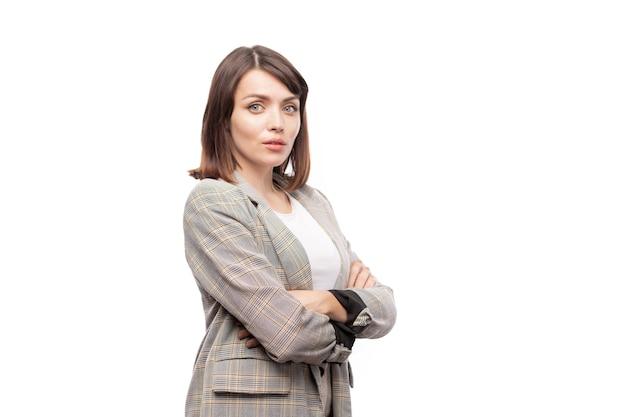 Junge elegante sekretärin oder lehrerin im anzug, die ihre arme auf der brust verschränkt, während sie isoliert steht Premium Fotos