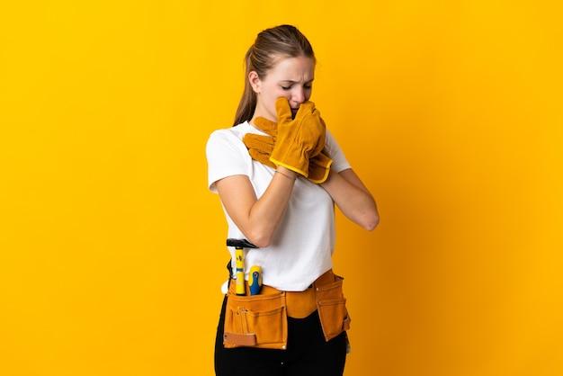 Junge elektrikerin, die auf gelber wand isoliert wird, leidet mit husten und fühlt sich schlecht Premium Fotos