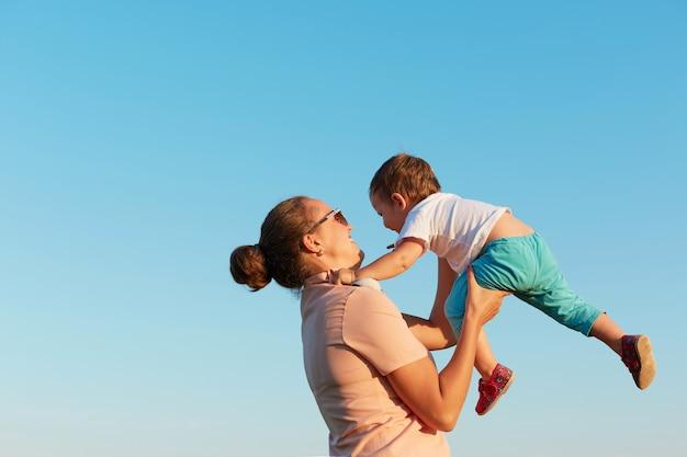 Junge entzückende frau mit haarknoten, die lässiges t-shirt hält, das kleinkind hält, zeit mit ihrer tochter, kleines mädchen fliegend im himmel in mamas händen, gegen klaren blauen himmel. Premium Fotos