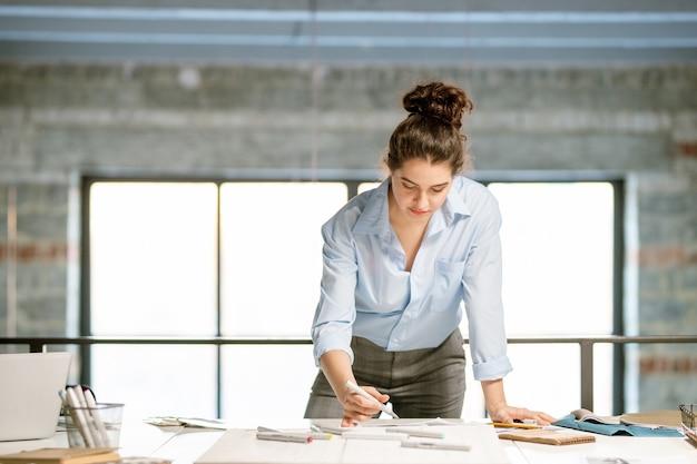 Junge ernsthafte designerin, die sich über modeskizzen auf dem schreibtisch beugt, während sie artikel für die neue kollektion auswählt Premium Fotos