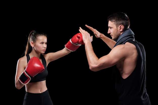 Junge ernsthafte fit frau in aktivkleidung und boxhandschuhen, die trainer während des kampfes schlagen Premium Fotos