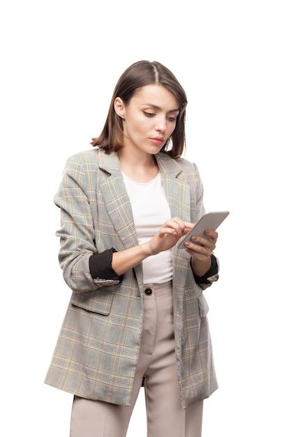 Junge ernsthafte mobile frau in der abendgarderobe, die im gerät beim durchsuchen von kontakten rollt Premium Fotos