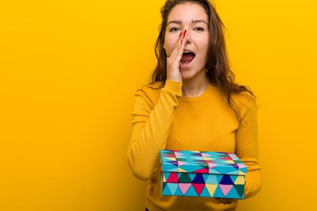 Junge europäische frau, die ein geschenkschreien aufgeregt zur front hält. Premium Fotos