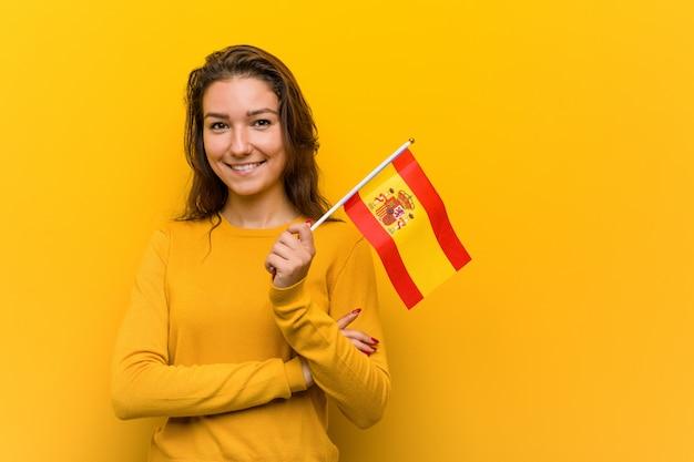 Junge europäische frau, die ein spanisches flaggenlächeln überzeugt mit den gekreuzten armen hält. Premium Fotos