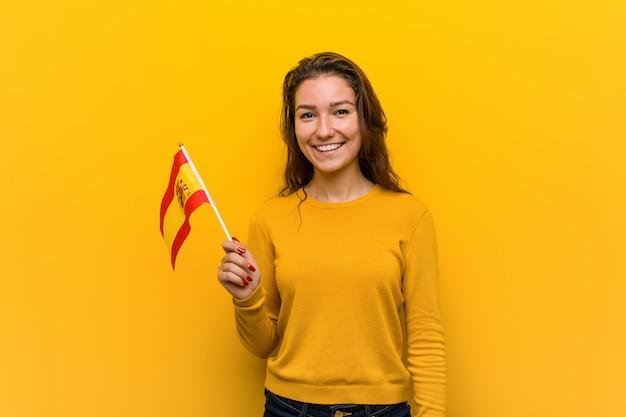 Junge europäische frau, die eine spanische flagge glücklich, lächelnd und nett hält. Premium Fotos