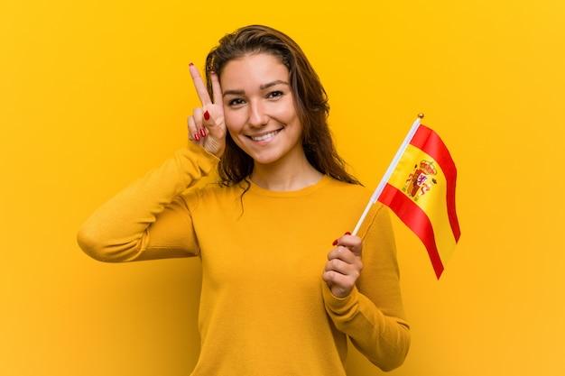 Junge europäische frau, die eine spanische flagge hält, die siegeszeichen zeigt und breit lächelt. Premium Fotos